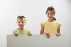 Two children holding a blank sign. You can add your own text Royalty Free Stock Photo