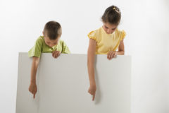 Two children holding a blank sign. And looking at it; you can add your own text Stock Photos
