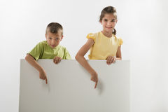 Two children holding a blank sign. And pointing at it; you can add your own text Royalty Free Stock Images