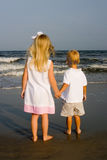 Two Children Holding Hands at the Beach. Two blond children holding hands at the beach, looking out at the water Royalty Free Stock Photos