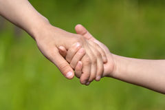 Two children holding hands each other, friendship concept. Two children holding hands each other on blurred background, closeup Royalty Free Stock Photography