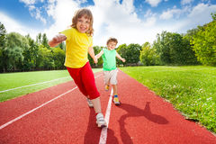 Two children holding hands running together Stock Photo