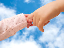 Two children holding hands on sky background. Royalty Free Stock Image