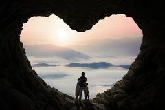 Two children hugging their father inside cave Royalty Free Stock Images