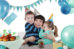 Two children hugging their mother at party table Royalty Free Stock Images