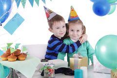Two children huging at blue party table Royalty Free Stock Photo