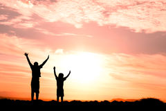 Two children jumping silhouette. Two children jumping for joy silhouetted sunset Stock Images