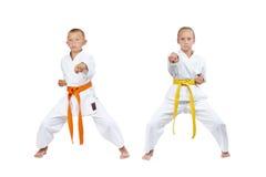 Two children in karategi beat kick gyaku-tsuki Stock Image
