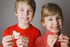 Two children keep wafer in hand and smile Stock Photography