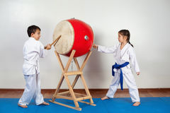 Two children in a kimono pounding the drum. Fighting position, active lifestyle, practicing fighting techniques stock images