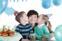 Two children kissing their mother at party table Stock Photo