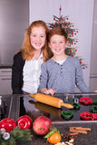 Two children in the kitchen preparing christmas bakery Stock Photos