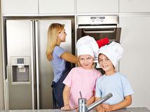 Two children in kitchen with their Stock Images