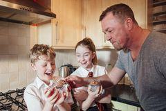 Mischevious Father Stealing some Cake. Two children are in the kitchen of their home after school. theyare eating cupcakes and the father is stealing some icing stock image
