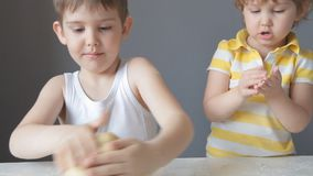 Two children knead the dough with their hands stock video footage