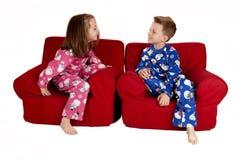 Two children laughing wearing winter pajamas sitting in red chai. Two children laughing wearing winter pajamas sitting royalty free stock images