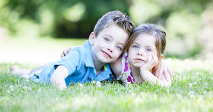 Two children laying in the grass. While embracing Stock Photo