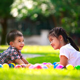 Two children are laying on green grass and smile Royalty Free Stock Photography