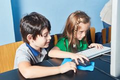 Two children learn concentrated at the computer stock photos