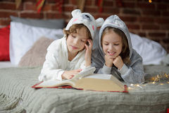 Two children lie on big bed and read fairy tales. Stock Image
