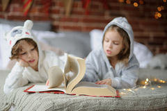 Two children lie on big bed and read fairy tales. Royalty Free Stock Images