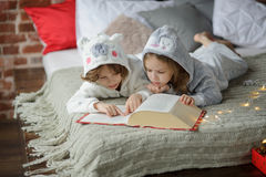 Two children lie on big bed and read fairy tales. Royalty Free Stock Photos