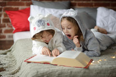 Two children lie on big bed and read fairy tales. Royalty Free Stock Image