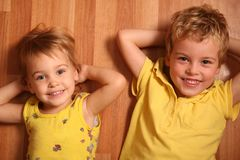 Two children lie on floor Stock Images
