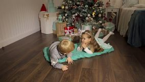 Two children lie on the floor near Christmas tree. Two small children lie on the floor next to a decorated Christmas tree stock video footage
