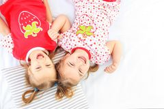 Two children lie in a pajamas bed. Copy space. The concept of ch. Two children lie in a pajamas bed. The concept of childhood, lifestyle, morning. Copy space stock photography