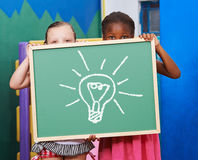 Two children with lightbulb on chalkboard Royalty Free Stock Image