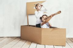 Two children little girls home in a cardboard ship play captains stock images