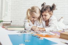 Two children, little girls of preschool age put the puzzle together on the floor royalty free stock photos