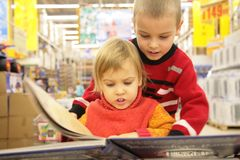 Two children look book in  store Royalty Free Stock Photos