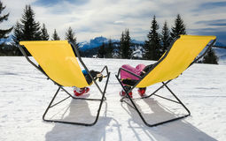 Two children on the lounge chairs on snow. Two children sitting on the lounge chairs on the snow, enjoying the beautiful view of the snowy mountain Stock Photo