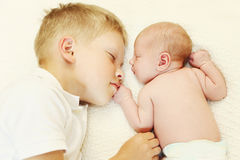 Two children lying on bed, eldest brother hugging youngest baby Royalty Free Stock Image