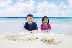 Two children lying on the coast. Photo of two happy children lying on the sand while laughing together at the coast Royalty Free Stock Image