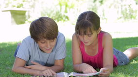 Two Children Lying In Garden Reading Magazine Together. Boy and girl lying in shade reading a magazine together and laughing.Shot on Canon 5D MkII at 25fps stock video footage
