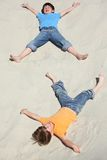 Two children lying on sand Royalty Free Stock Photos