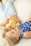 Two Children Lying Upside Down On Sofa At Home Stock Image