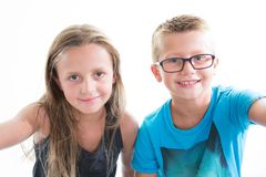 Two children make photo selfie with smartphone on white background wall. Two children make photo selfie with cell phone smartphone on white background wall stock image