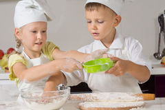Two children making pastry for pizza bases. Two young children in chefs uniforms making pastry for pizza bases flouring the dough so that they can roll in out on stock image