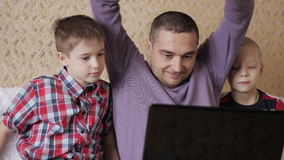 Two children and a man. Father and two sons, looking at a laptop on the couch in the living room stock video footage