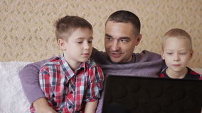 Two children and a man. Father and two sons, looking at a laptop on the couch in the living room stock footage