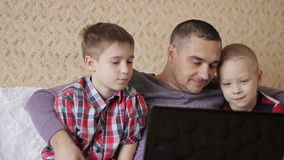 Two children and a man. Father and two sons, looking at a laptop on the couch in the living room stock video