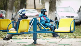 Two children on a merry-go-round. Sitting on the seats wrapped up warmly against the cold weather spinning around stock video