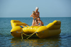 Two children with mom on the dinghy sailing at sea in summer Stock Photos