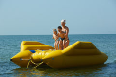 Two children with mom on the dinghy sailing at sea in summer Stock Image