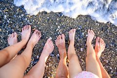 Two children, mother and father legs on the seashore. In a summer sunny day. Family holiday. Travel Stock Photos