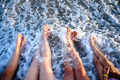 Two children, mother and father legs on the seashore. In a summer sunny day. Family holiday. Travel Stock Images